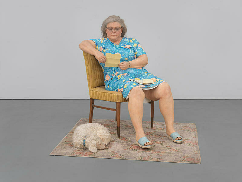 A sculpture of a woman reading on a chair next to a sleeping dog.