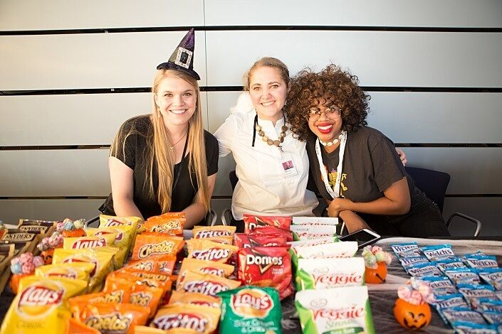 Party goers pose in front of snacks.