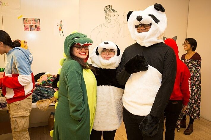 A teen dressed as a dinosaur and two people dressed as panda bears.
