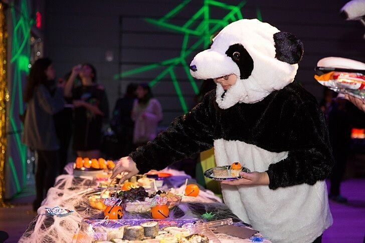 A teen dressed as a panda bear puts snacks on a plate.