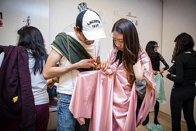 Two teens cut fabric to create a costume.