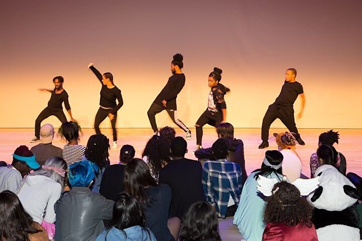 A dance group performs on stage.