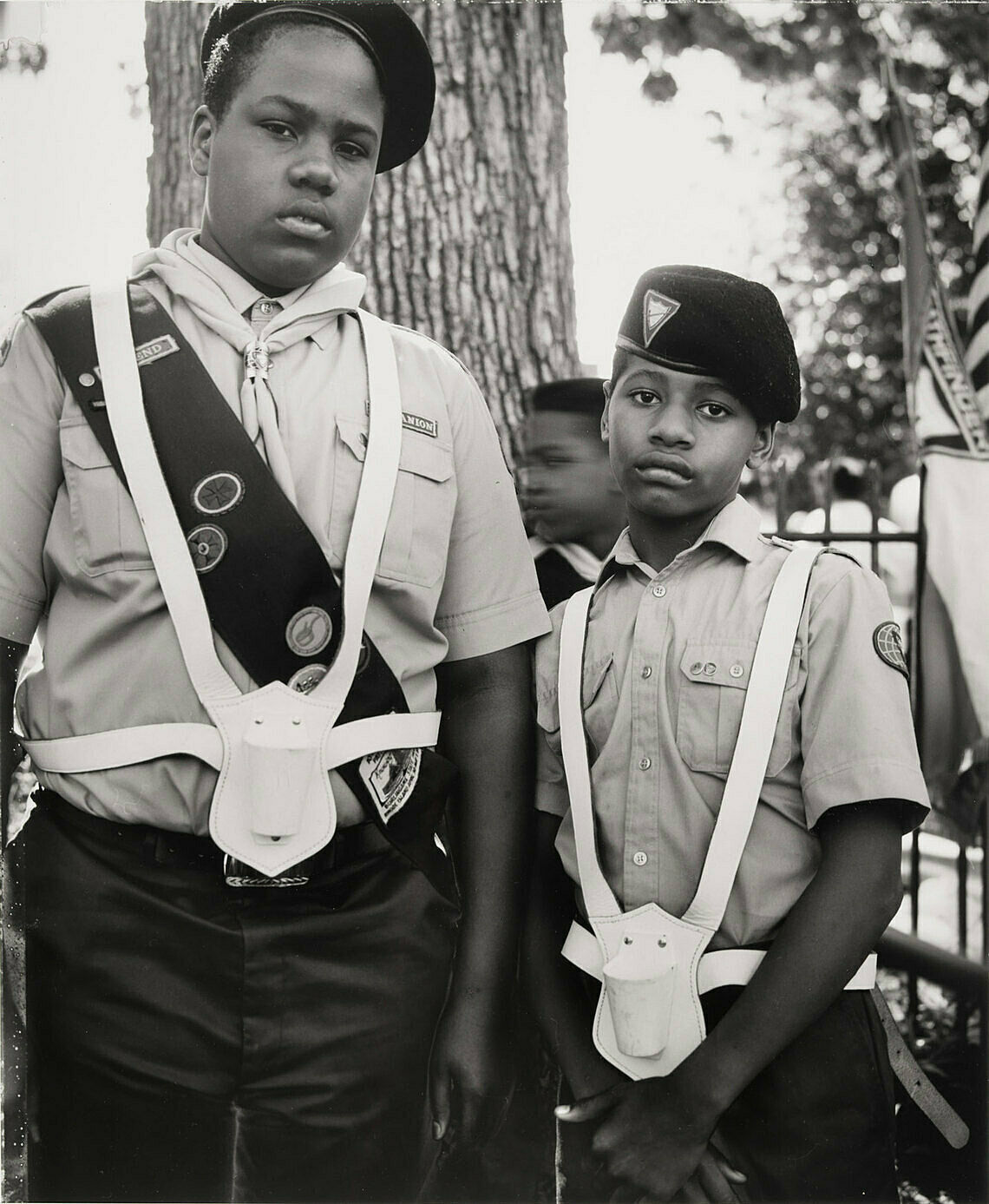 A black and white photograph by Dawoud Bey. Two young African American boys wear scout uniforms, with somber faces.