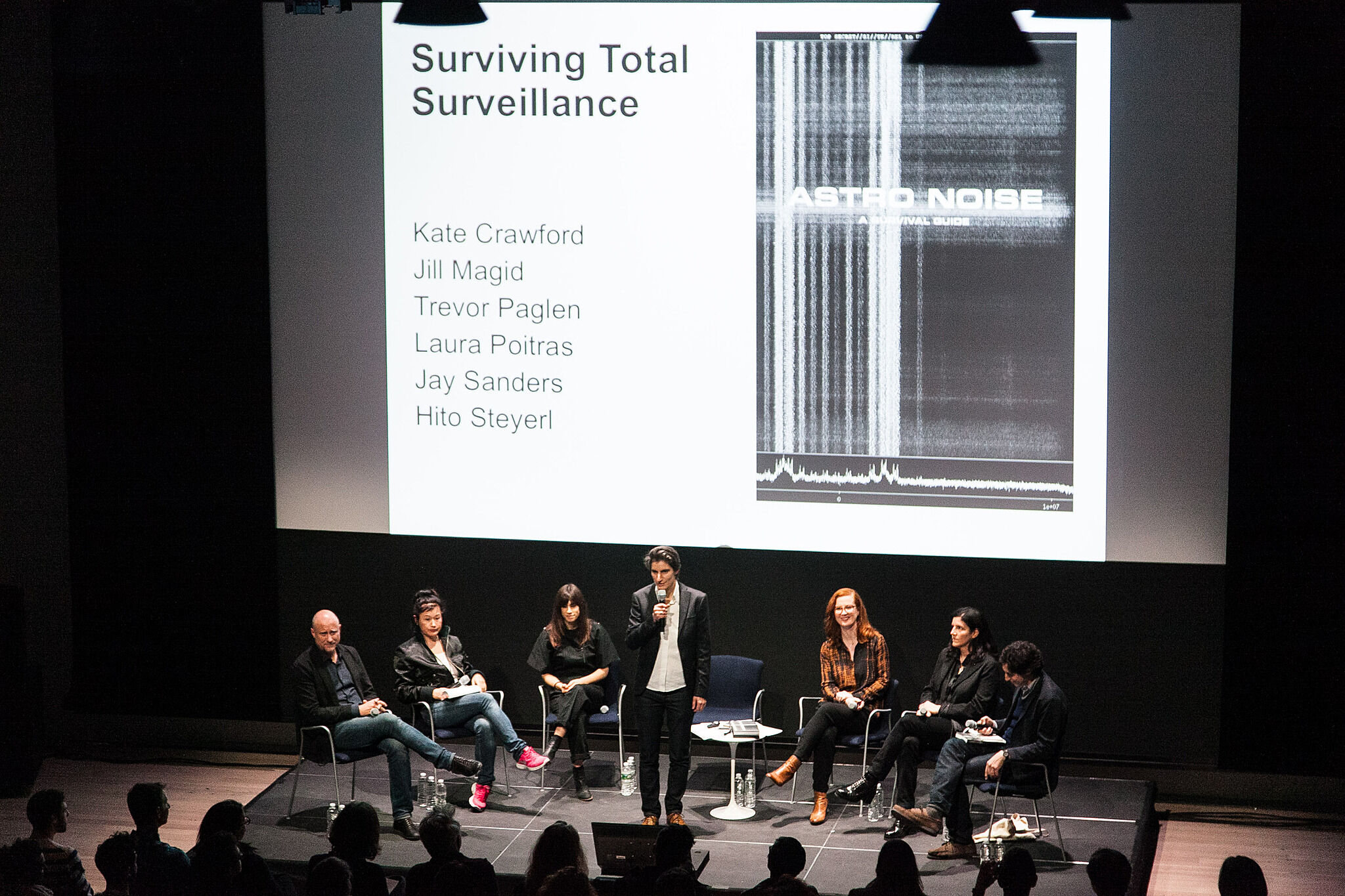 A panel of speakers engage with the audience