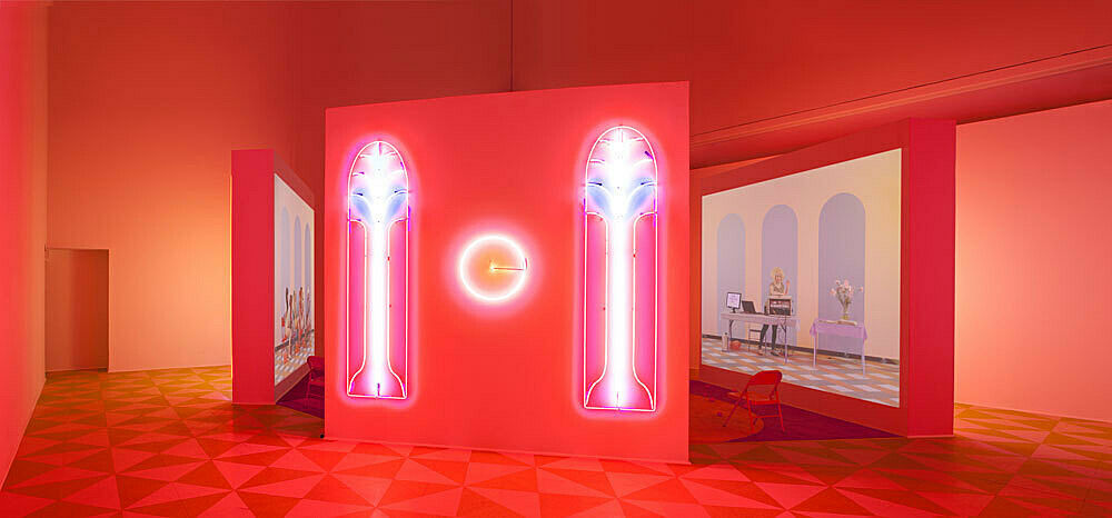 An neon and video installation by Alex Da Corte and Jayson Musson. Neon lighs in bright orange, red and purple stretch the length of a wall; a projected image is visible