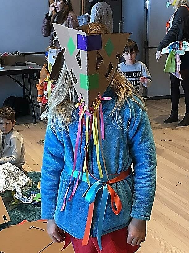 A girl wears a mask she made in a workshop