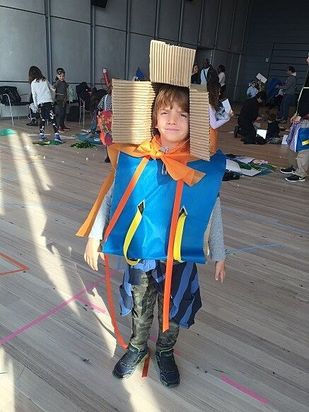 A child poses in a costume made out of cardboard