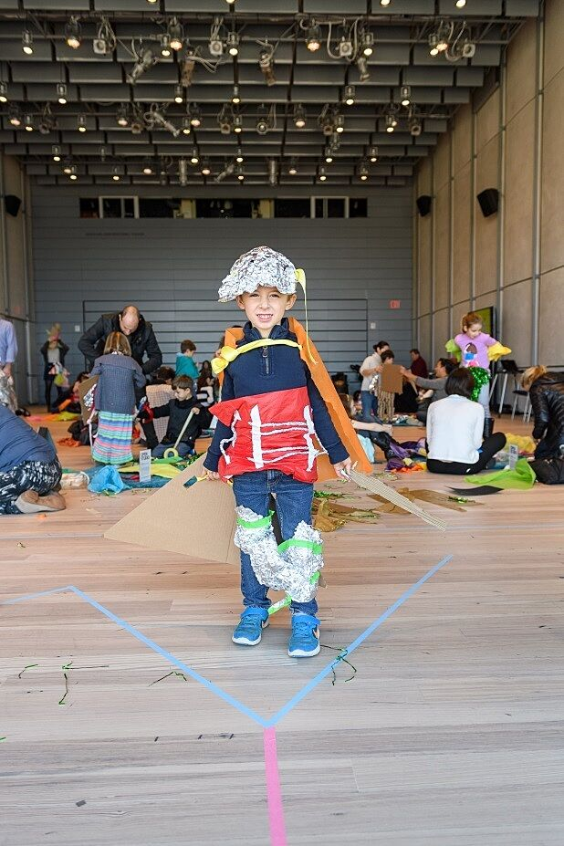 A boy models his costume in the workshop
