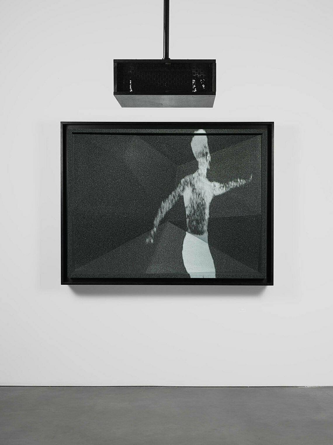 An installation view of a work by Josiah McElheny. A video projection depicts a blurry figure in black and white tones