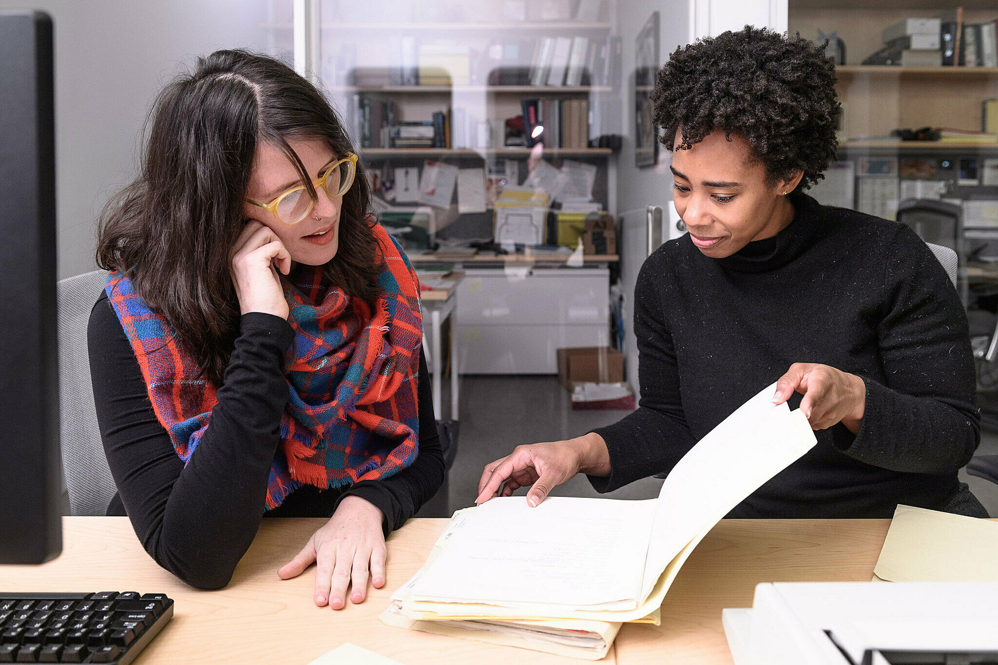 Two artists perusing a book in the archives.