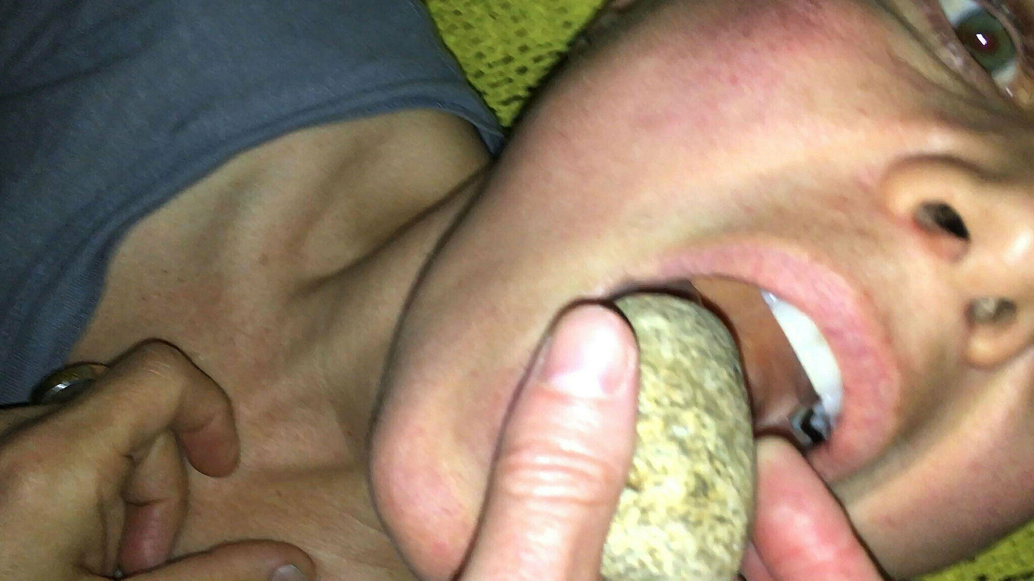 A video still of person putting a rock in their mouth.