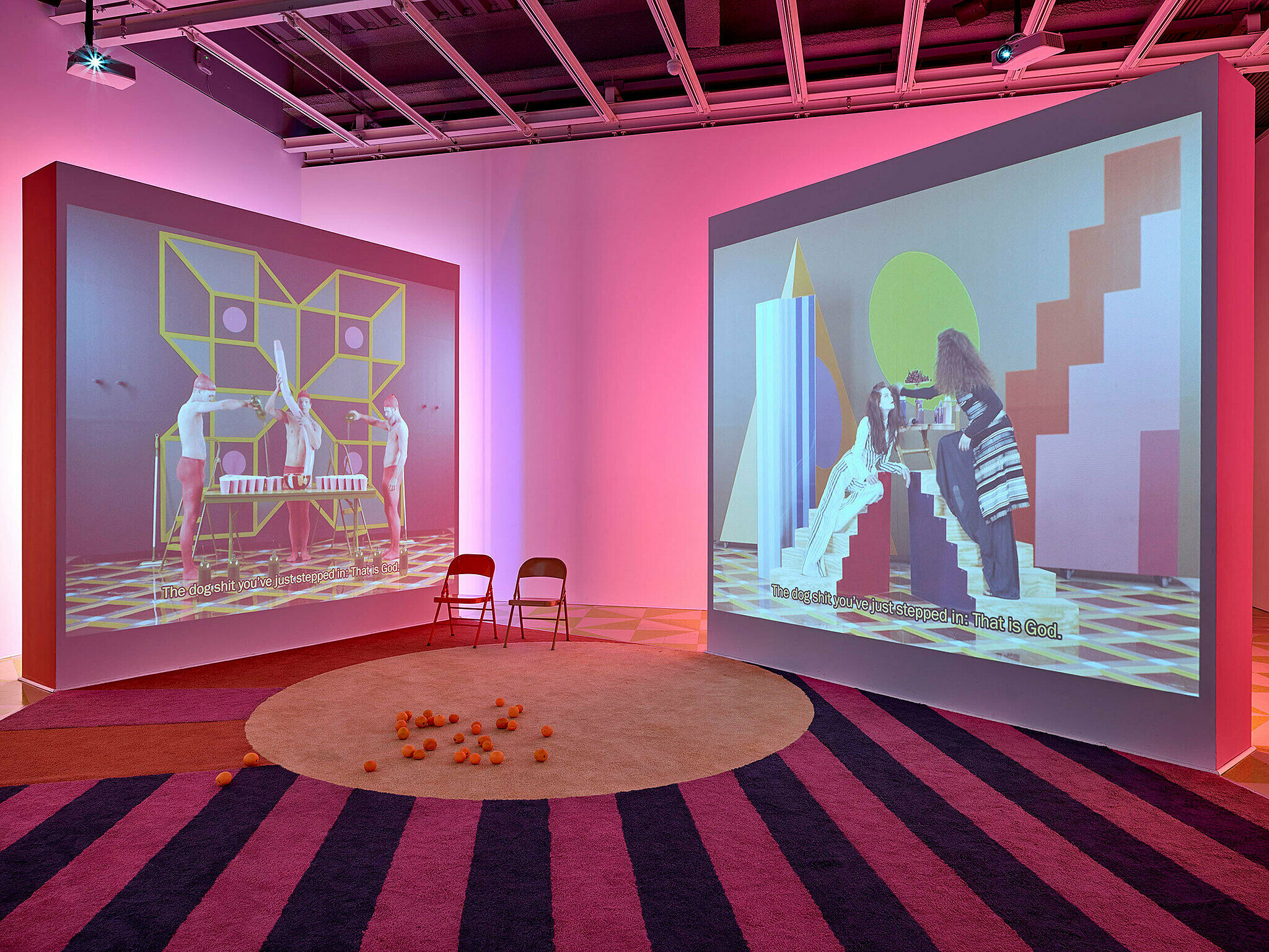 Installation view of Easternsports; two videos projected on large screens in neon pink room