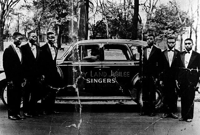 The Blind Boys of Alabama posed in front of a black car