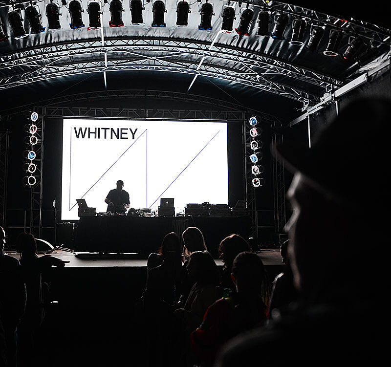 The Whitney logo on a big screen