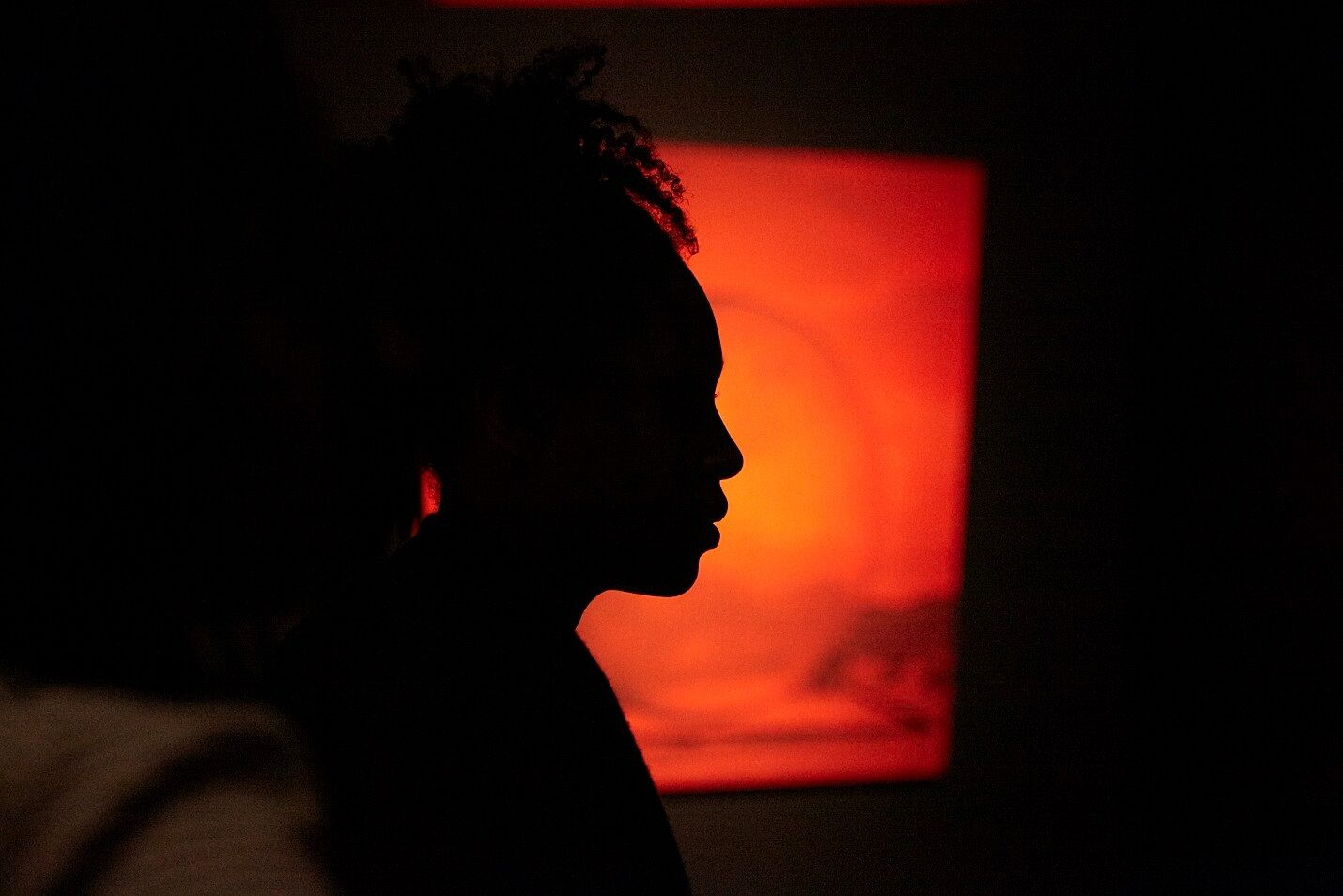 profile of a womans face with orange light