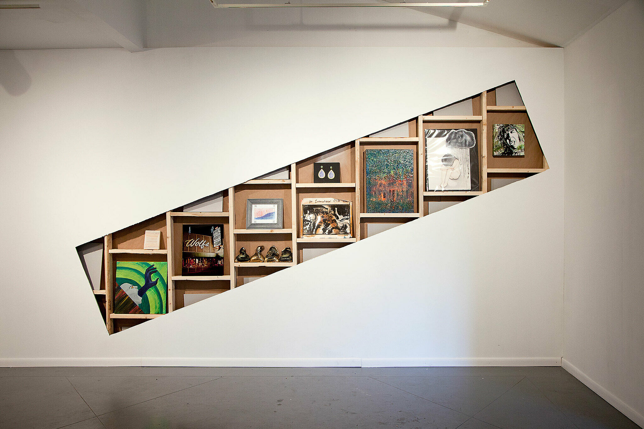 Various artworks inside wooden compartments