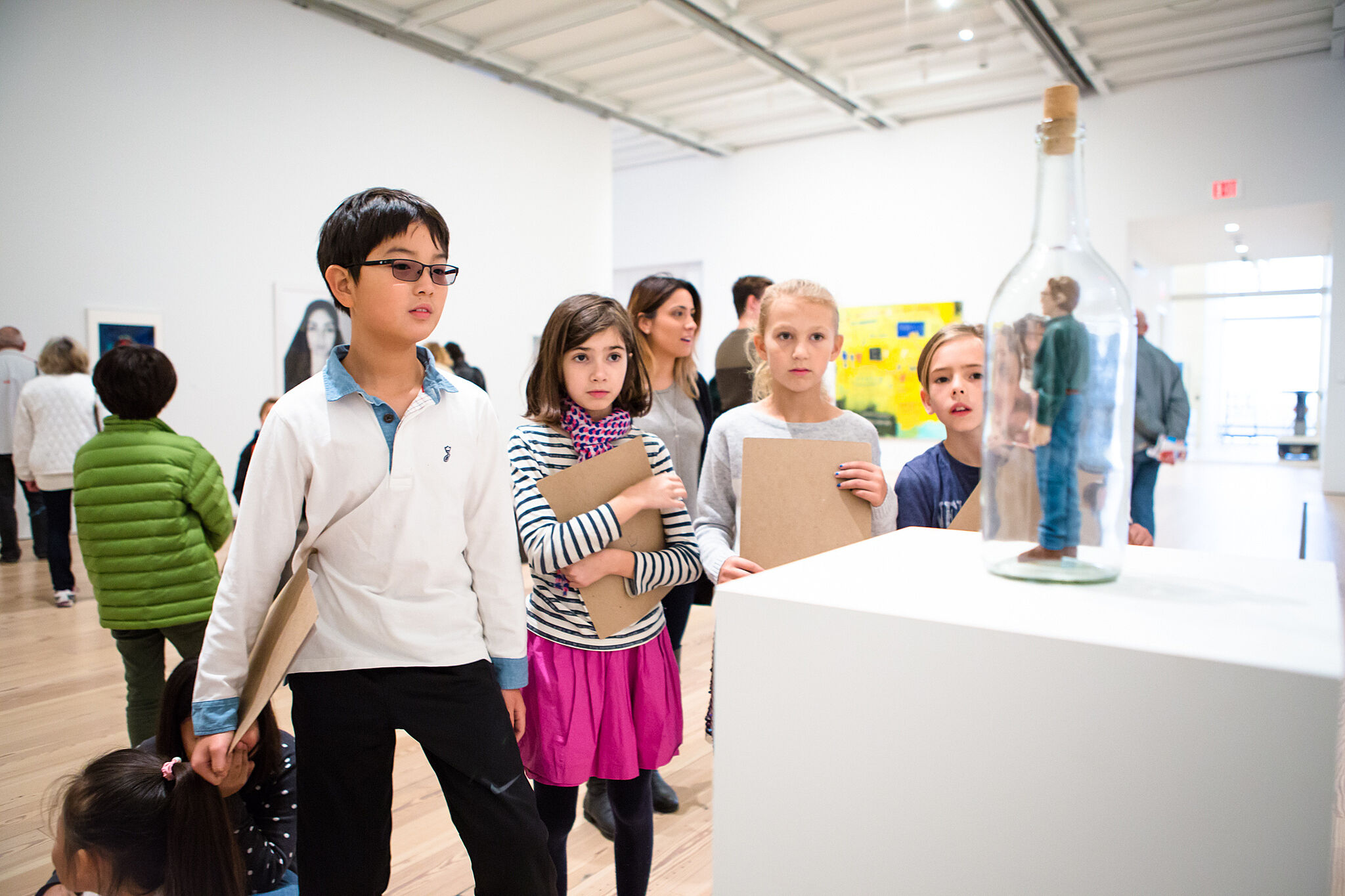 students look at statue in gallery