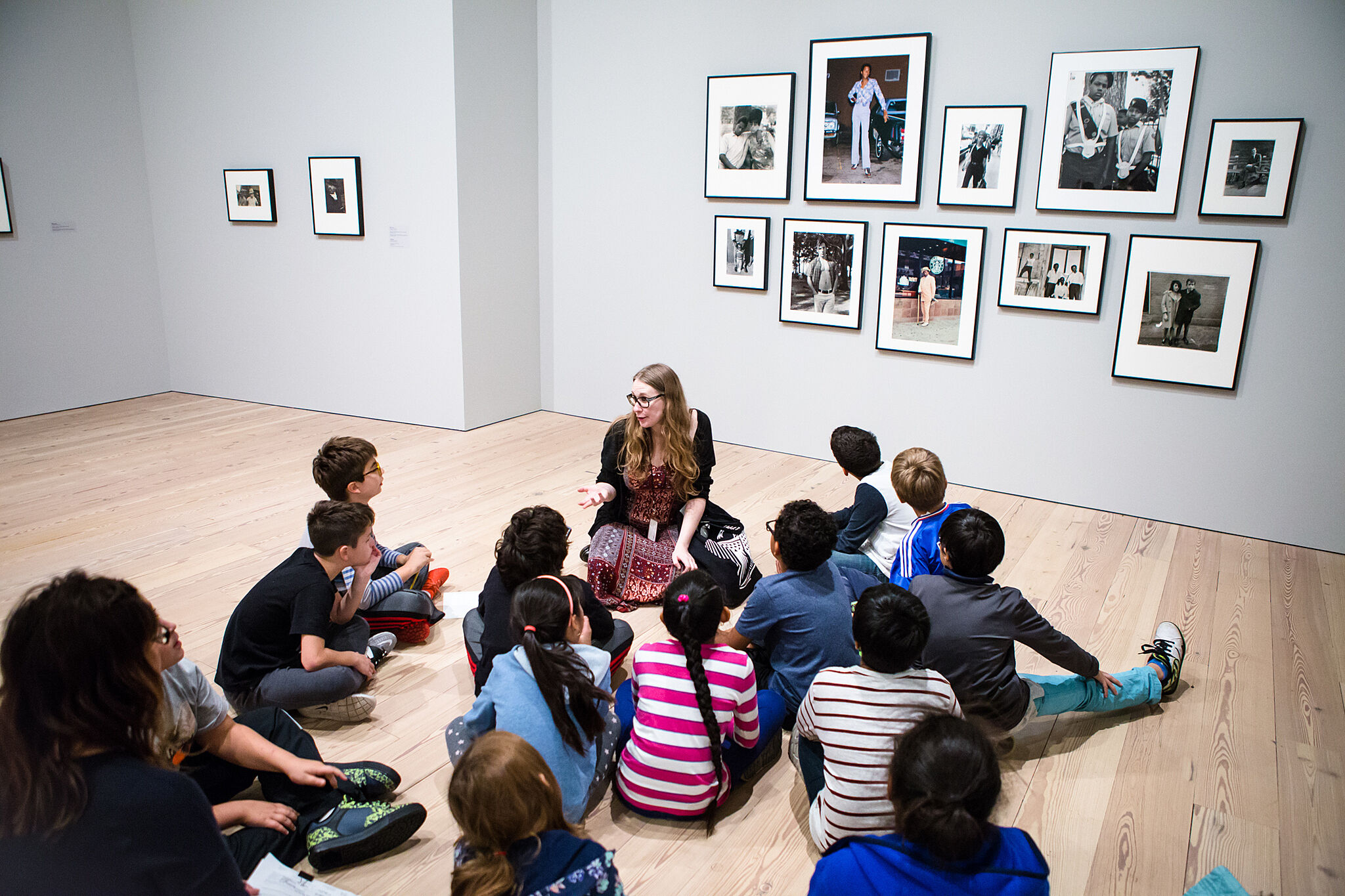 students sitting looking at paintings on wall