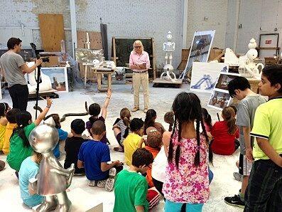 students sit in studio around artist