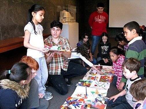 children standing showing art to students