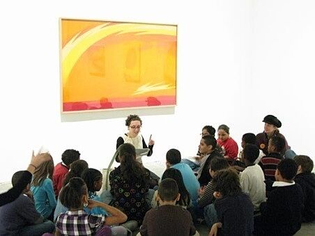 students sitting in front of painting and educator