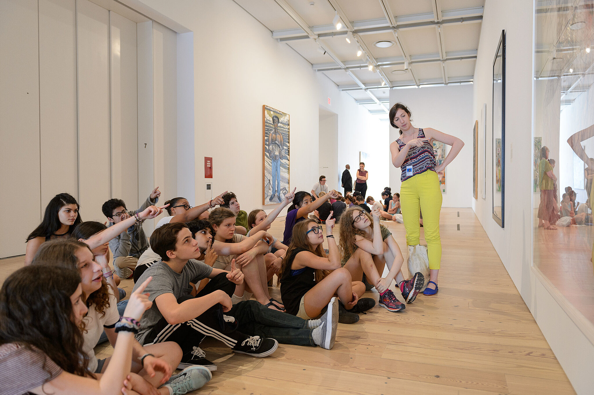 group of students sit and point at art in gallery
