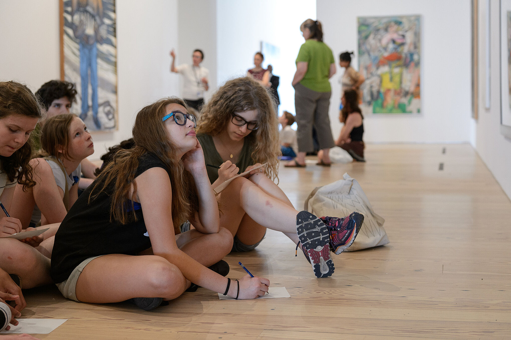 students sit looking up at artwork on gallery floor
