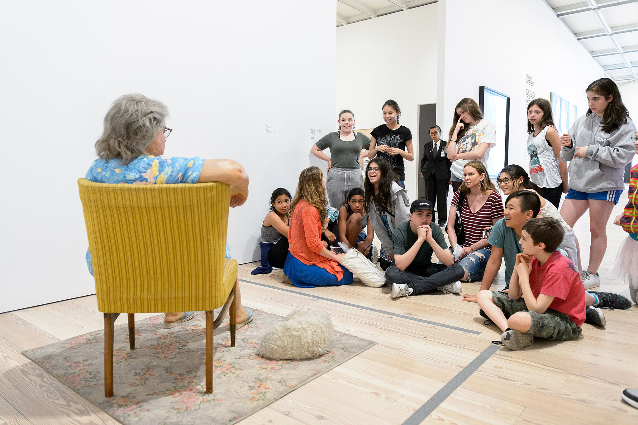 students sitting in front of sculpture