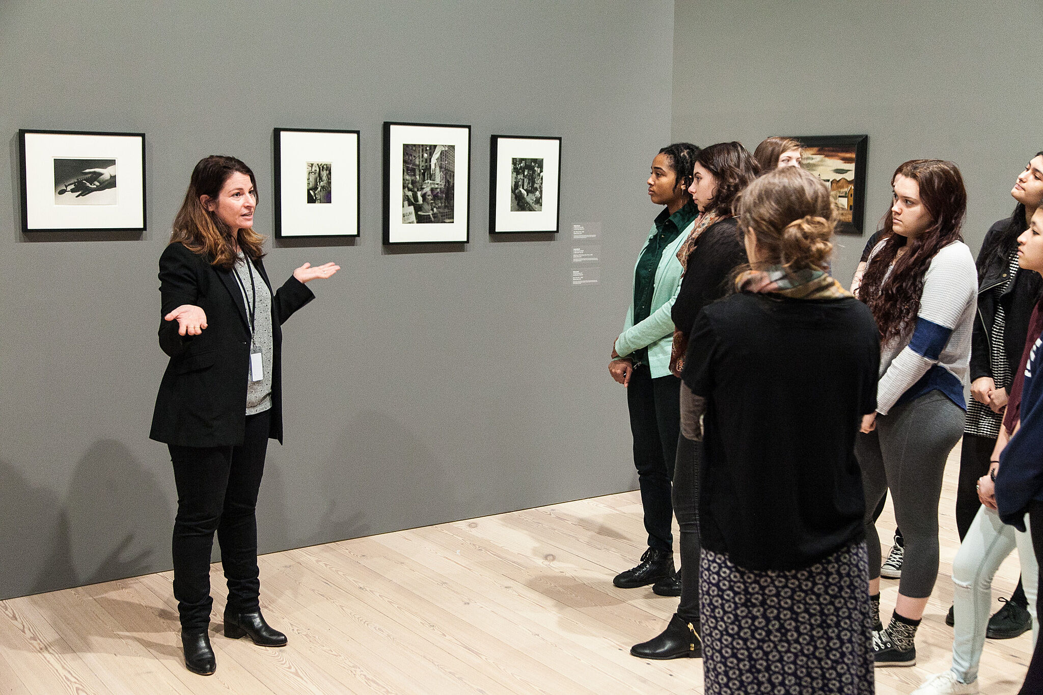 woman speaking to students in front of paintings