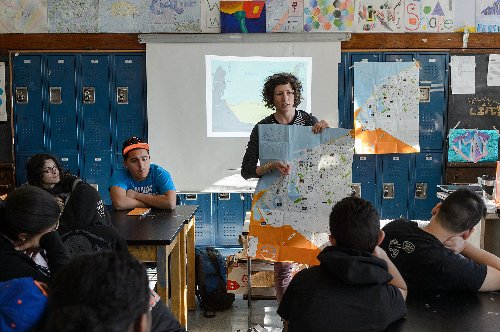 Artist presenting her map to class of students.