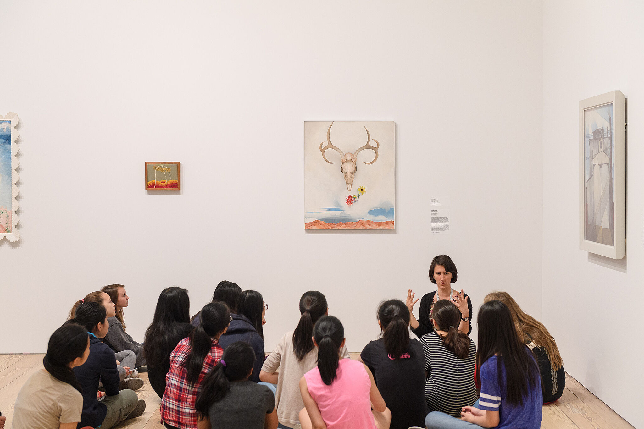 Students sitting and listening to teacher in gallery.