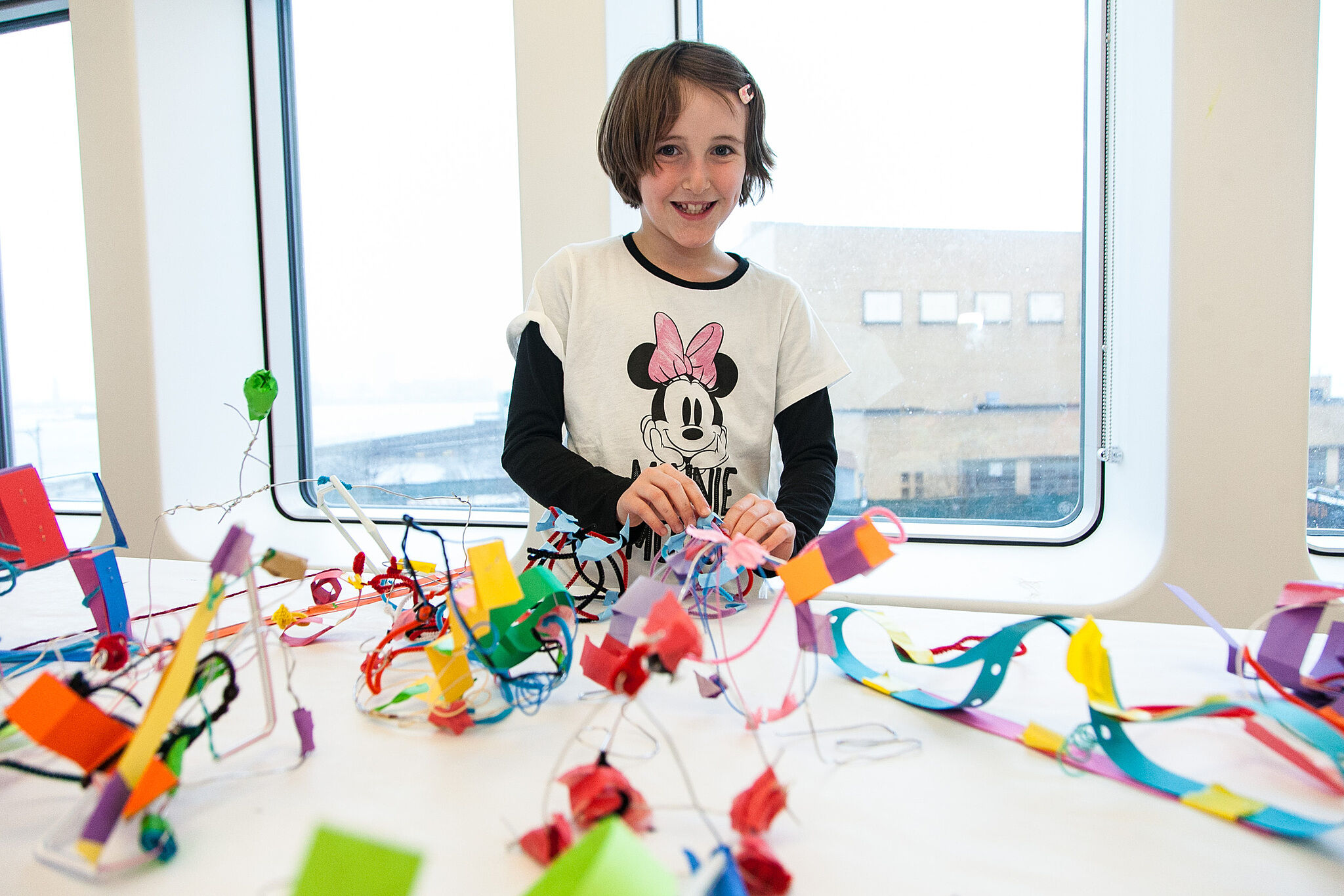 Child smiling in front of colorful crafts