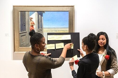 Students holding board in front of painting.