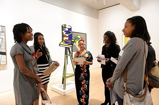Students discussing artwork with parents in gallery.