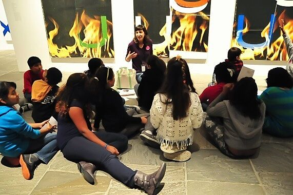 Students sitting on gallery floor in front of art.