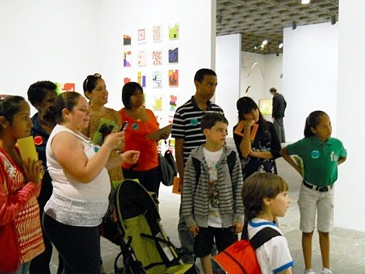 Students and families standing in gallery.