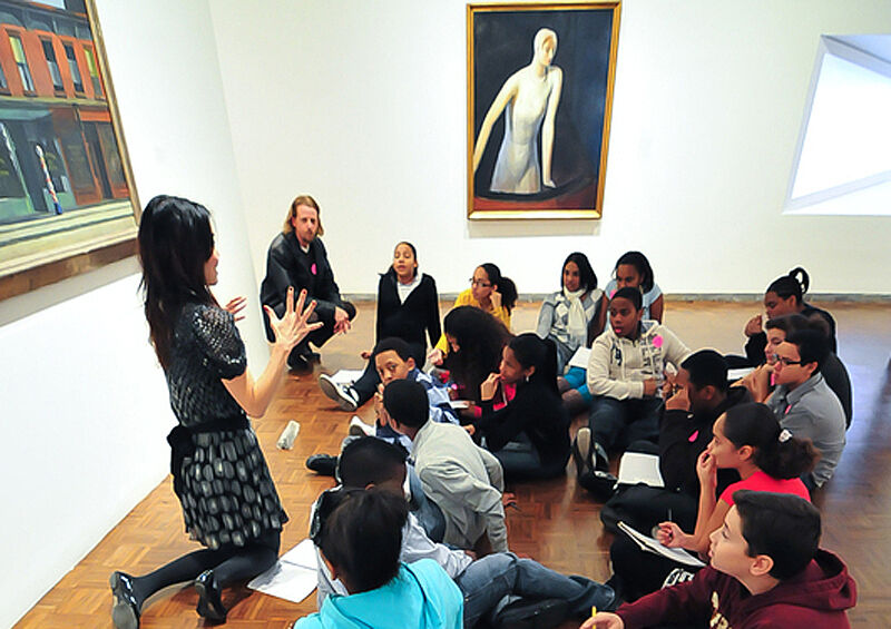 Educator sits up and explains in front of artwork.