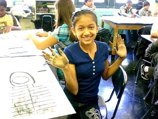 Girl with charcoals on hands holding up hands.
