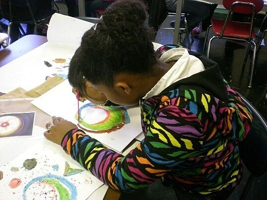 Student intently focused on her watercolor painting.