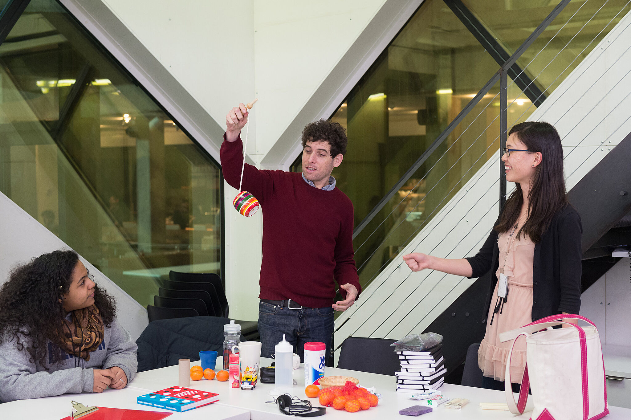 The artist demonstrates an object in front of two teens.