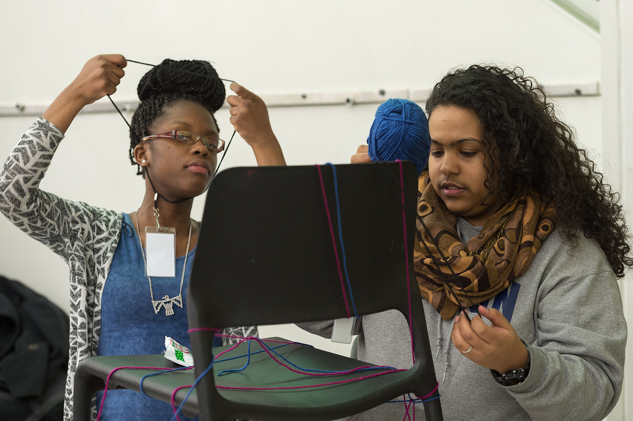 Two students use yarn and a chair to work on a project.