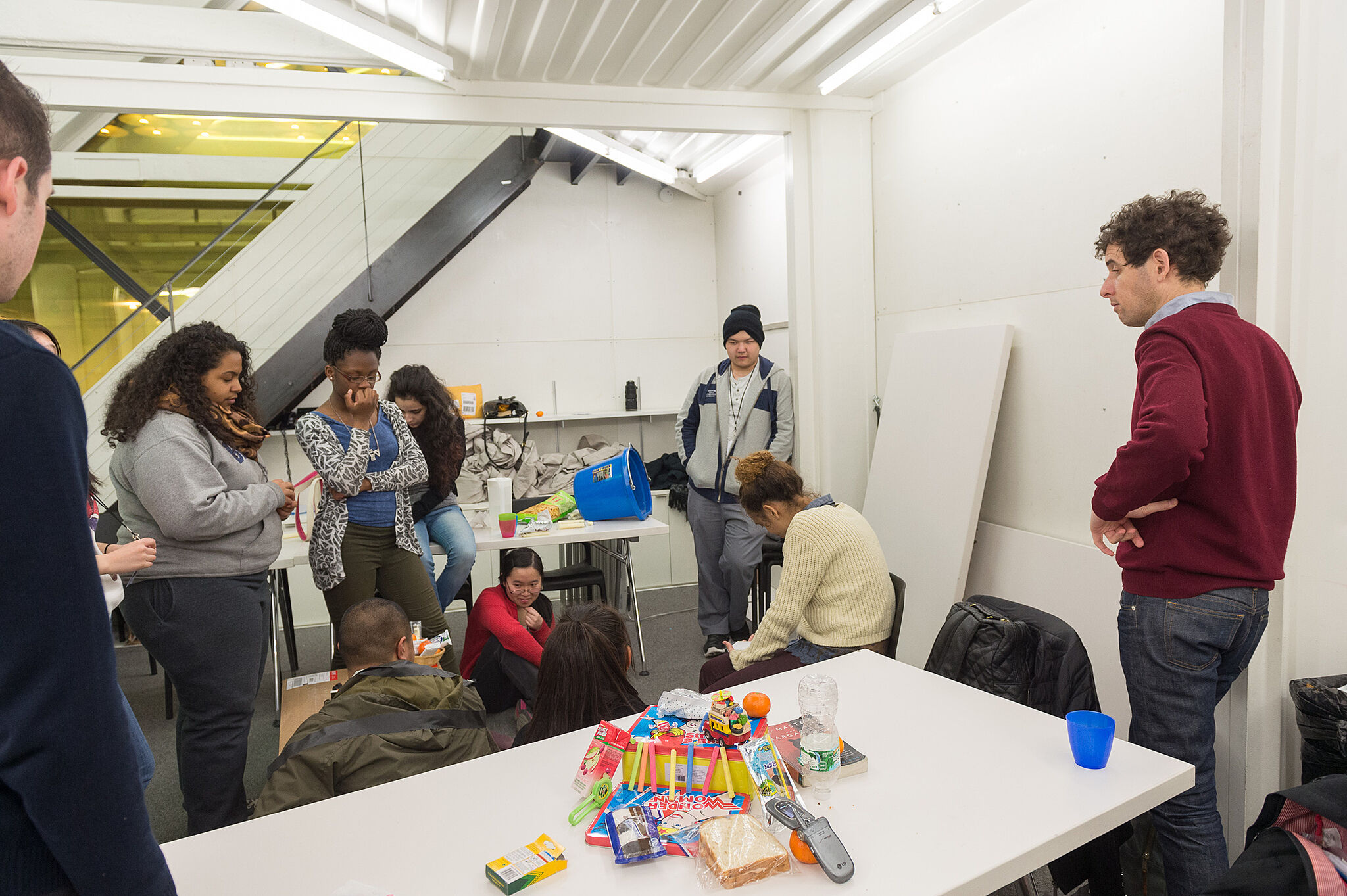 The artist works with students on a project with random objects.