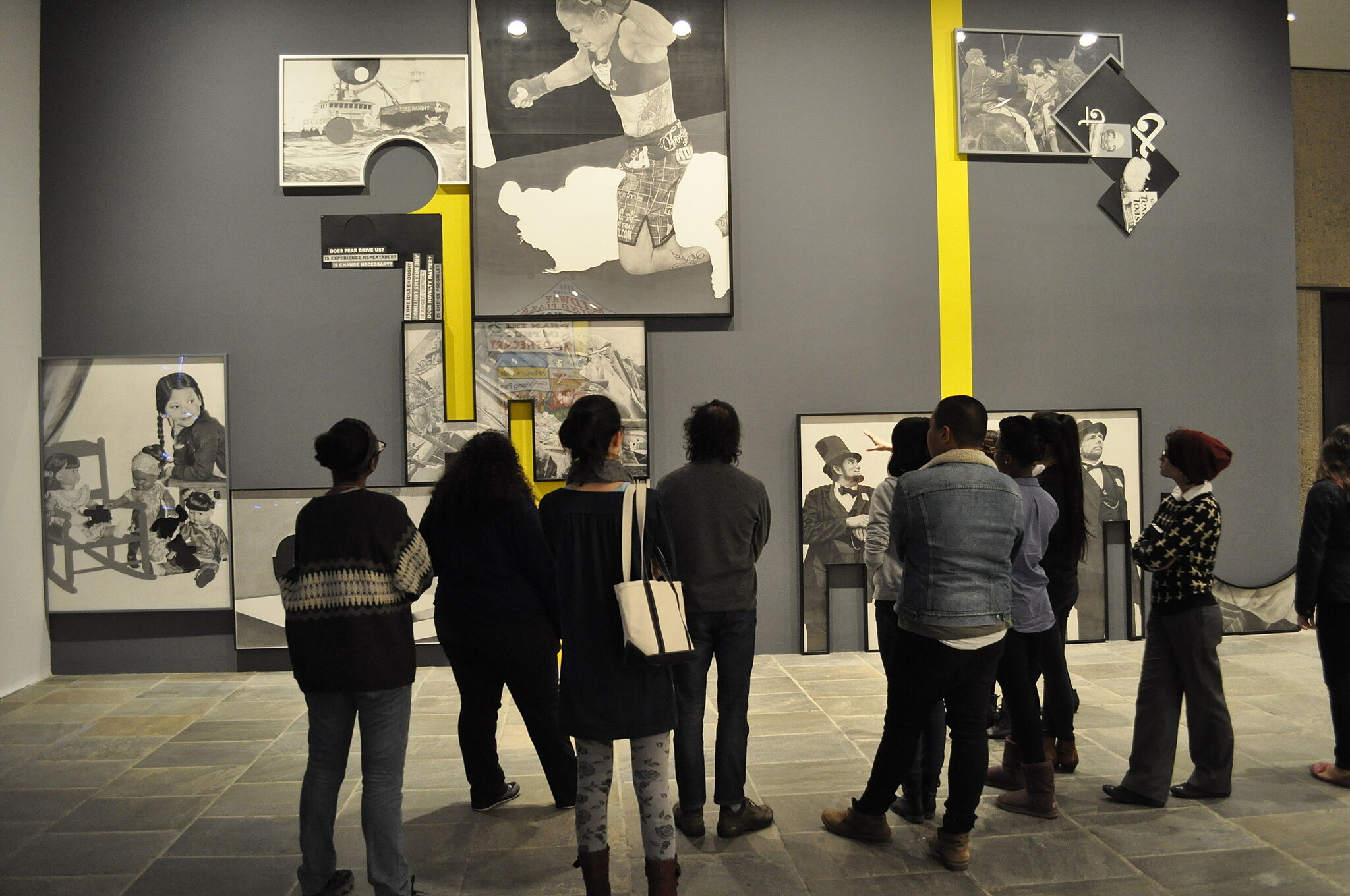 A youth group looks at large photos in the Biennial exhibit.