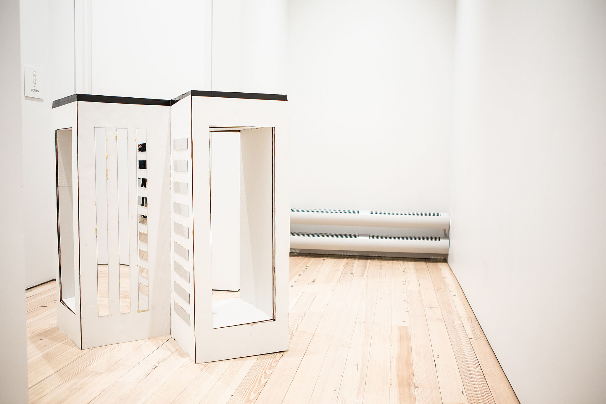 Photo of tall boxes in a gallery.