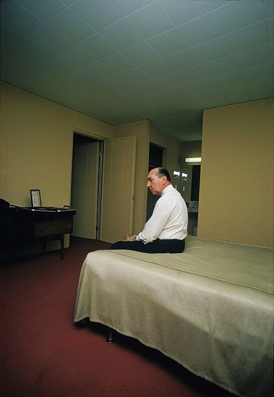 Man sitting on a bed in a room with red carpet.