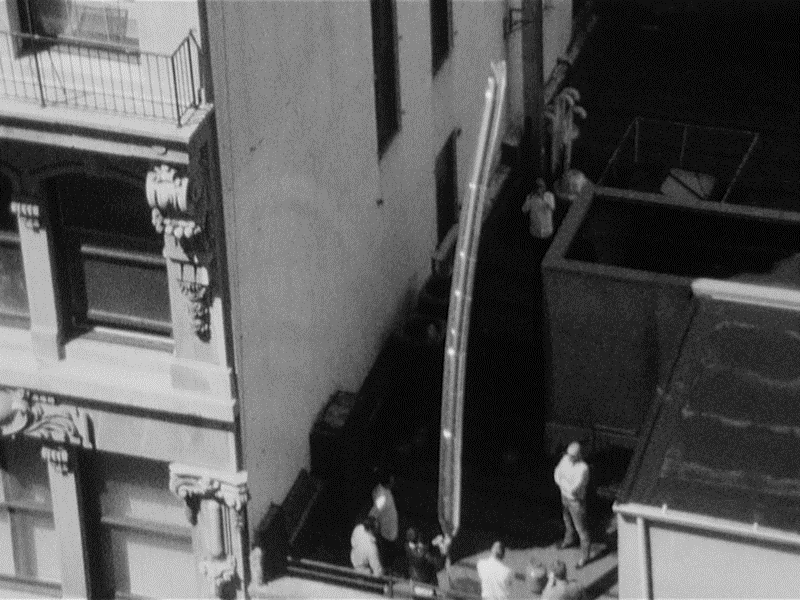 Black and white photo of people on building.