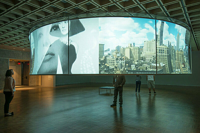 Projected panorama and woman's face on a large curved structure.