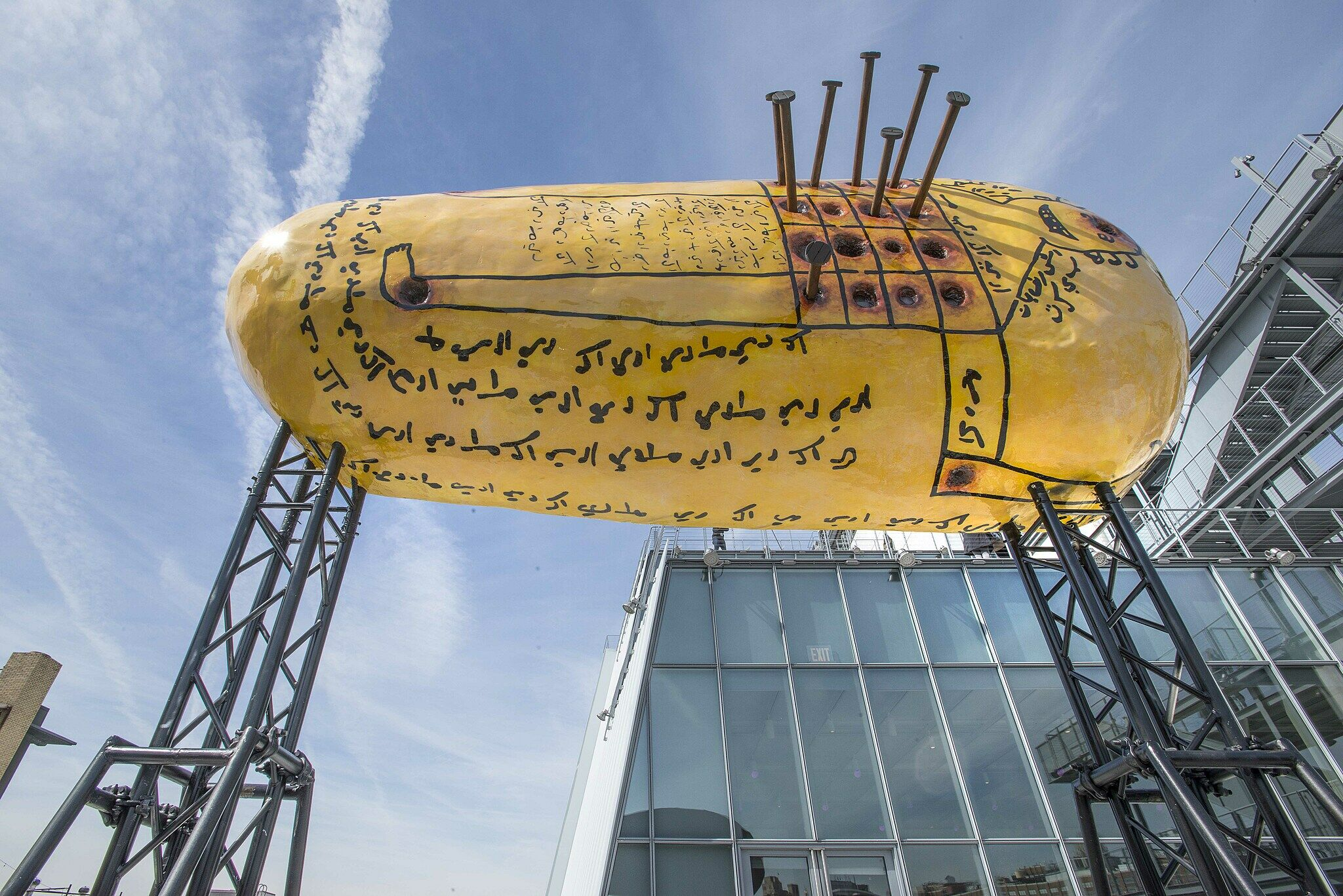 Large yellow gourd-shaped sculpture covered in black writing and nails