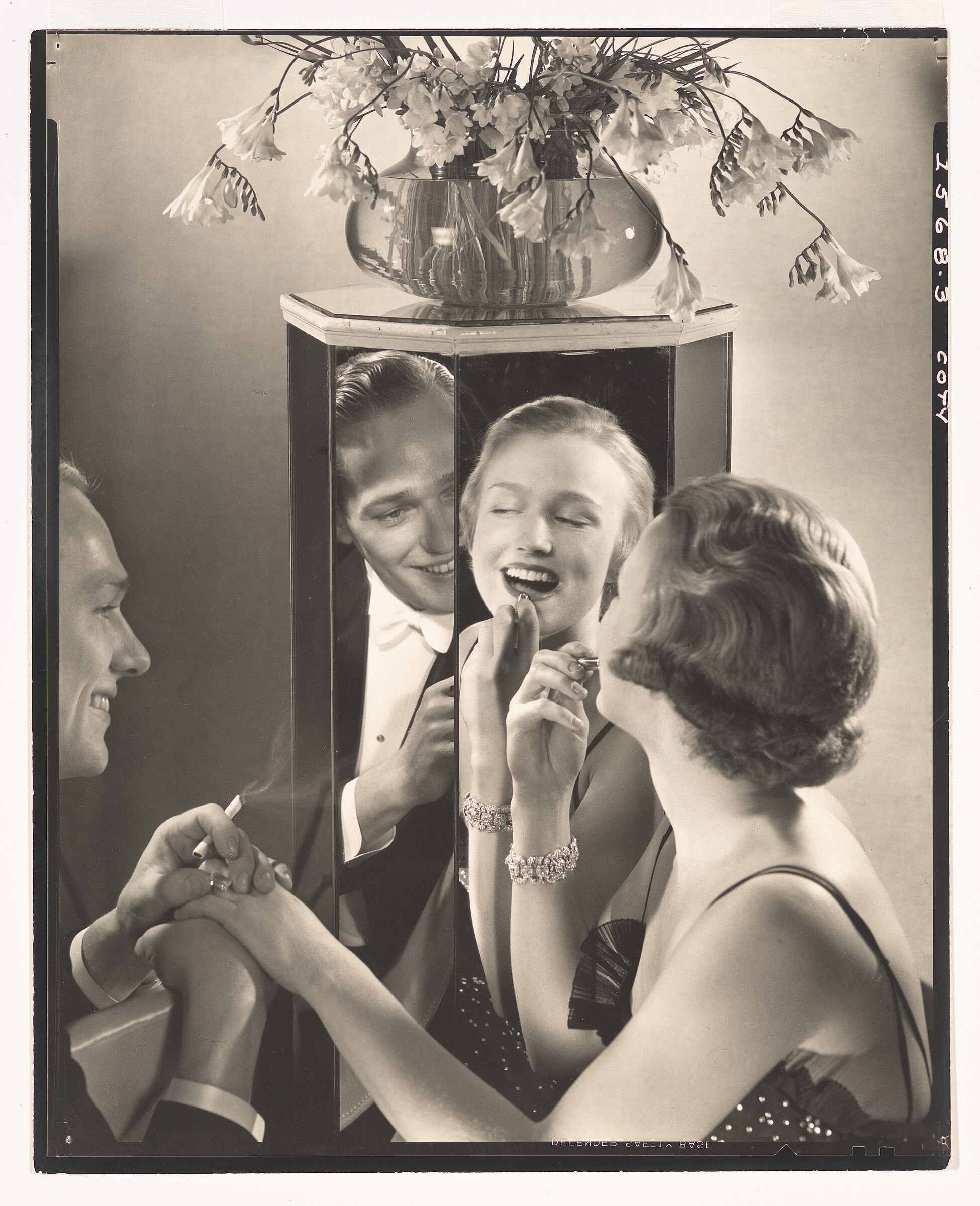 Woman applying make up in mirror with man near in black and white photo.