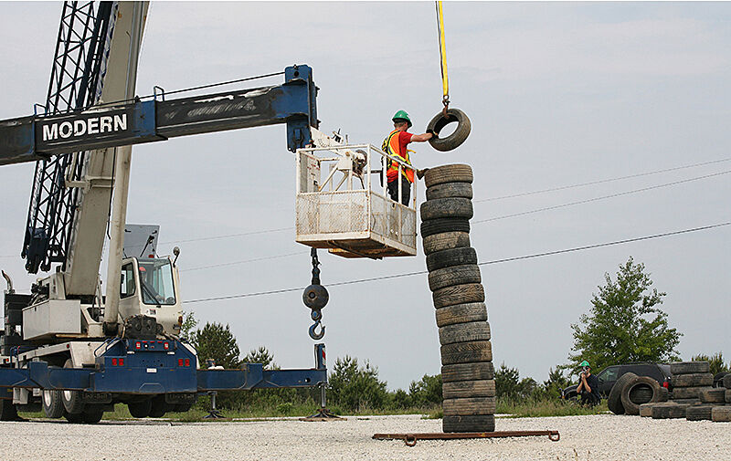 A construction worker holds a tire over a sculpture from a crane.